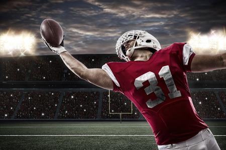 スタジアムでボールをつかまえる赤い制服のフットボール選手.