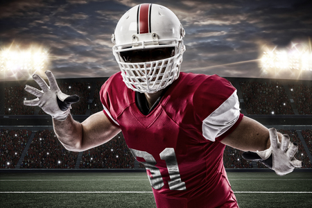 football tackle: Football Player with a red uniform making a tackle on a Stadium.