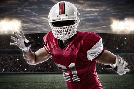 jugador de futbol: Jugador de f�tbol con un uniforme rojo haciendo un tackle en un estadio.