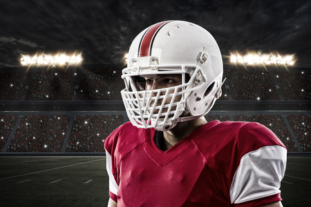 football tackle: Close up of a Football Player with a red uniform on a Stadium. Stock Photo
