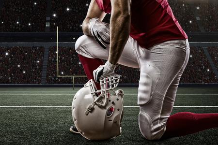 jugador de futbol: Jugador de f�tbol con un uniforme rojo de rodillas, en un estadio.