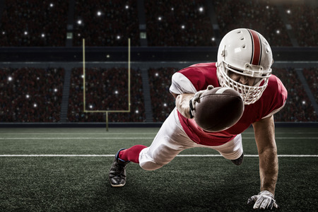 Football Player with a red uniform scoring on a Stadium. Stock Photo