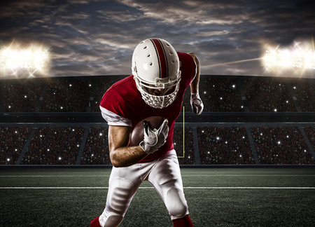 football tackle: Football Player with a red uniform Running on a Stadium. Stock Photo