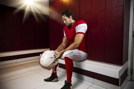 jugador de futbol: Jugador de f�tbol con un uniforme rojo sentado en el vestuario. Foto de archivo