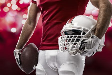 jugador de futbol: Jugador de f�tbol con un uniforme rojo sobre un fondo de luces de color rojo.
