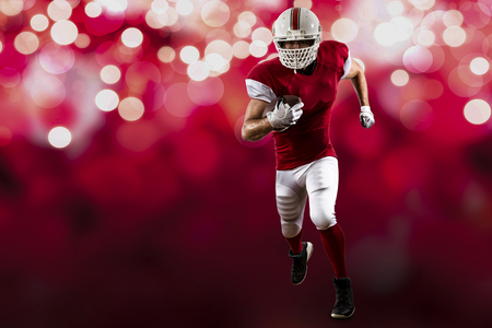 football tackle: Football Player with a red uniform Running on a red lights background.