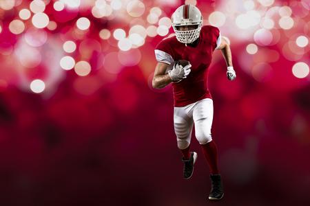 jugador de futbol: Jugador de f�tbol con un uniforme rojo que se ejecuta en un fondo de luces de color rojo.