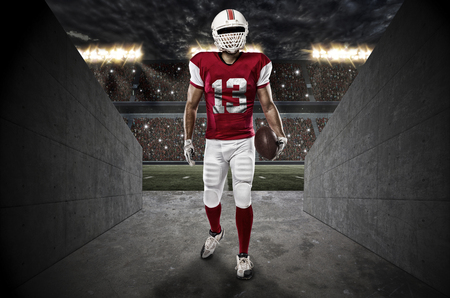 Football Player with a red uniform entering a stadium tunnel.