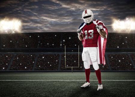 jugador de futbol: Jugador de f�tbol con un uniforme rojo y una bandera americana, en un estadio.