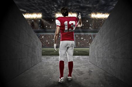 jugador de futbol: Jugador de f�tbol con un uniforme rojo que sale de un t�nel Stadium.