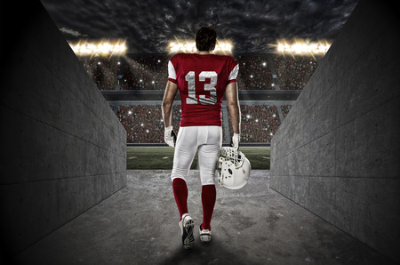 american football ball: Football Player with a red uniform walking out of a Stadium tunnel.