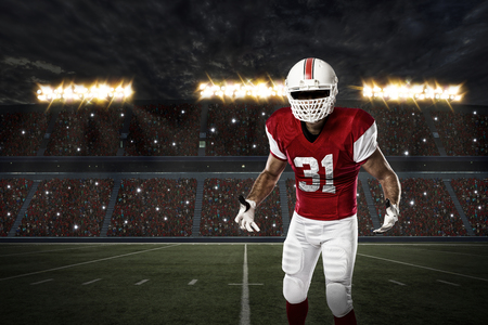 football tackle: Football Player with a red uniform on a stadium.