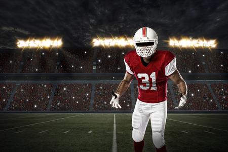 jugador de futbol: Jugador de f�tbol con un uniforme rojo en un estadio. Foto de archivo
