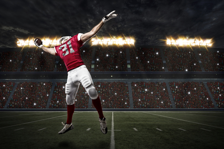 player: Football Player with a red uniform catching a ball on a stadium.