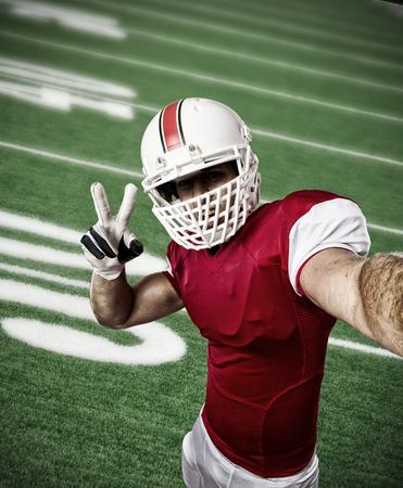 jugador de futbol: Jugador de f�tbol con un uniforme rojo haciendo una Autofoto en un campo de f�tbol.