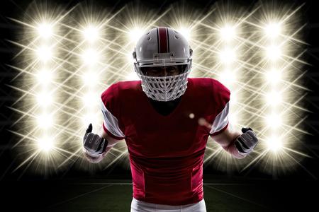 jugador de futbol: Jugador de f�tbol con un uniforme rojo frente a las luces. Foto de archivo