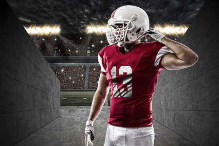 player: Football Player with a red uniform on a stadium tunnel.