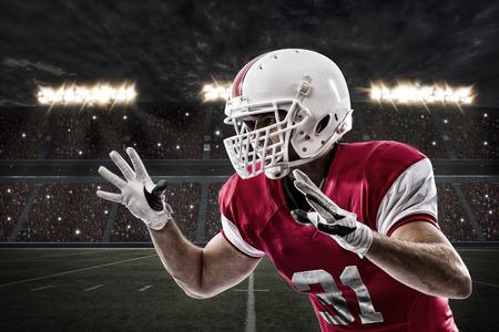 playing football: Jugador de f�tbol con un uniforme rojo haciendo un tackle en un estadio.