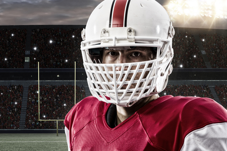 player: Close up of a Football Player with a red uniform on a Stadium. Stock Photo