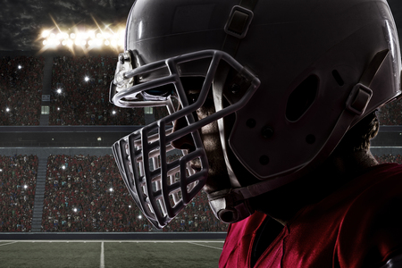 football tackle: Close up of a Football Player with a red uniform on a stadium.