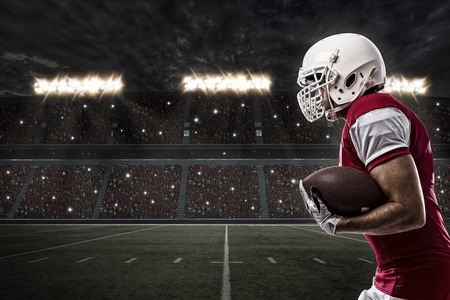 american football: Football Player with a red uniform Running on a Stadium. Stock Photo