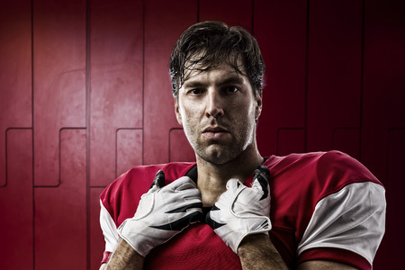 football tackle: Football Player with a red uniform on a Locker roon.