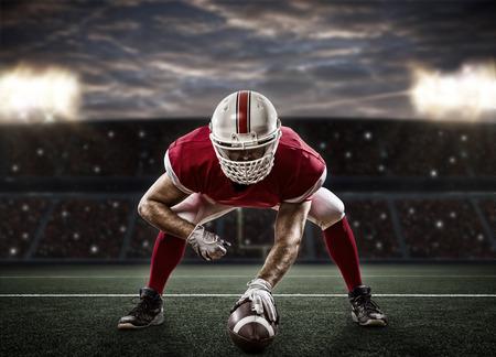 jugando futbol: Jugador de f�tbol con un uniforme rojo en la l�nea de golpeo, en un estadio.