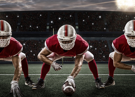 football tackle: Football Players with a red uniform on the scrimmage line, on a stadium.