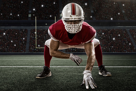 football tackle: Football Player with a red uniform on the scrimmage line, on a Stadium.