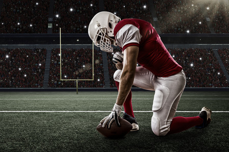 tackle: Football Player with a red uniform on his knees, on a Stadium. Stock Photo