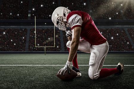 futbolista: Jugador de fútbol con un uniforme rojo de rodillas, en un estadio.