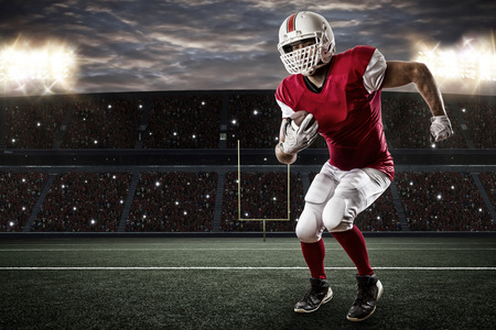 jugador de futbol: Jugador de f�tbol con un uniforme rojo que se ejecuta en un estadio. Foto de archivo