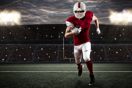 player: Football Player with a red uniform Running on a Stadium. Stock Photo