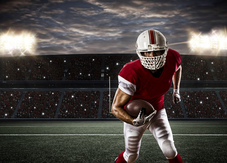 american football ball: Football Player with a red uniform Running on a Stadium. Stock Photo