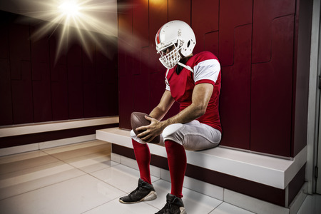 seated: Football Player with a red uniform seated in locker room.