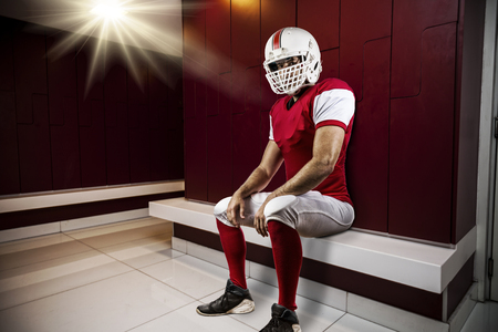 player: Football Player with a red uniform seated in locker room.