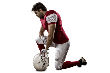 jugando futbol: Jugador de f�tbol con un uniforme rojo de rodillas, sobre un fondo blanco.