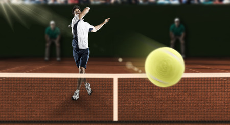 tennis stadium: Tennis player playing on a clay tennis court.
