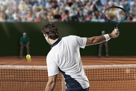 jugando tenis: Tenista devolver una pelota en una cancha de tierra batida.