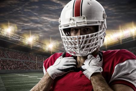jugando futbol: Jugador de fútbol con un uniforme rojo en un estadio. Foto de archivo