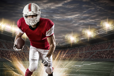 masculinity: Football Player with a red uniform running on a stadium.