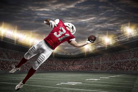 スタジアムでボールをつかまえる赤い制服のフットボール選手。