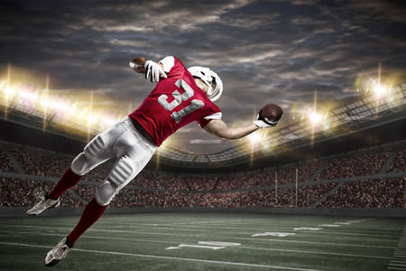 sports uniform: Football Player with a red uniform catching a ball on a stadium.