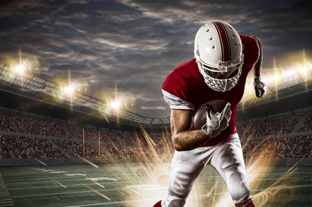 football tackle: Football Player with a red uniform running on a stadium.