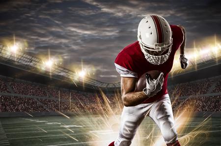 jugando futbol: Jugador de fútbol con un uniforme rojo que se ejecuta en un estadio. Foto de archivo