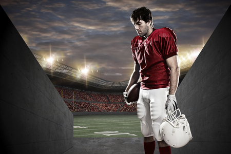 american football ball: Football Player with a red uniform on a tunnel to a stadium.