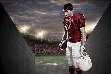 football players: Jugador de fútbol con un uniforme rojo en un túnel a un estadio.