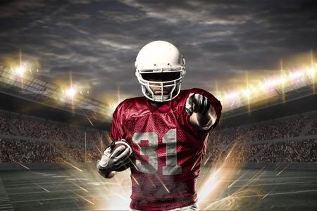 football players: Jugador de fútbol en un uniforme rojo que celebra en un estadio.