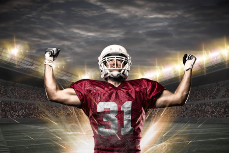 masculinity: Football Player on a Red uniform celebrating on a Stadium.