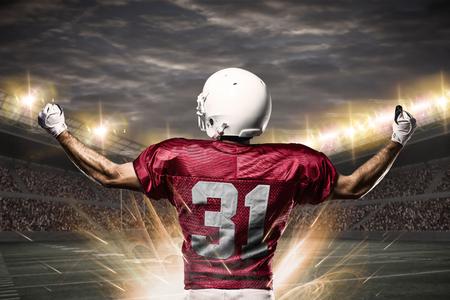 hombre deportista: Jugador de fútbol en un uniforme rojo que celebra en un estadio.